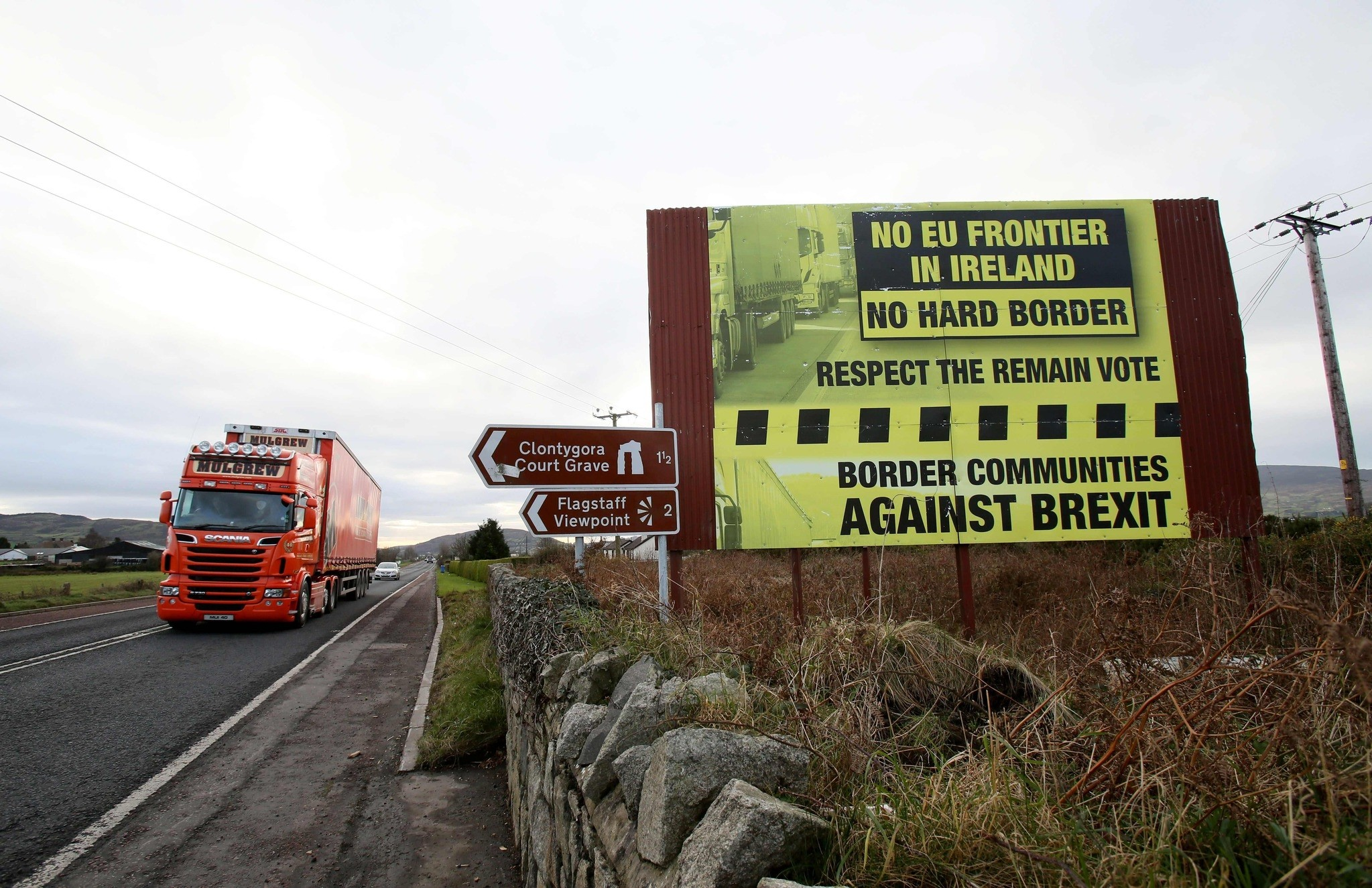 This photo shows traffic crossing the border into Northern Ireland from the Irish Republic alongside a Brexit Border poster on the Dublin road Co Armagh border, between Newry in Northern Ireland and Dundalk in the Irish Republic. (AFP Photo)