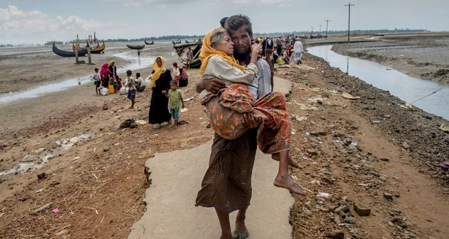 A Rohingya Muslim man walks towards a refugee camp carrying his mother after crossing over from Myanmar into Bangladesh, Sept. 16.