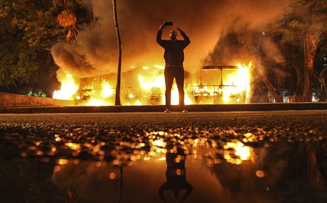 A man takes a selfie in front as protesters burn buses during a strike in Rio de Janeiro, Brazil, 28 April 2017. (EPA Photo)