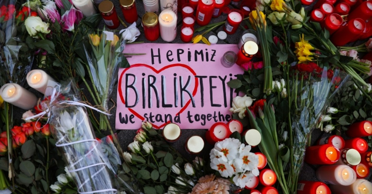 A placard, flowers and candles are pictured during a vigil for the victims of a shooting, in Hanau, near Frankfurt, Germany, February 21, 2020. (Reuters Photo)