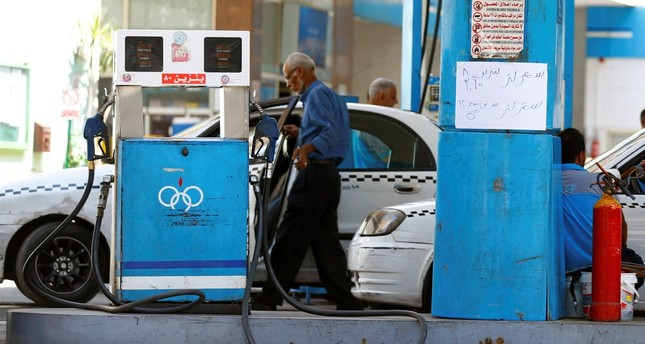 A sign at a petrol station shows fuel price in Cairo, Egypt. The sign reads: Price of 92-octane gasoline has been put up from 3.50 Egyptian pounds per liter to 5 Egyptian pounds. 80-octane increased to 3.65 pounds per liter from 2.3 pounds.