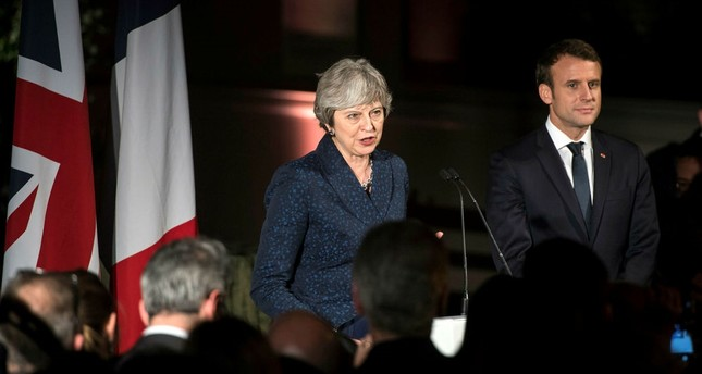 British Prime Minister Theresa May L and French President Emmanuel Macron R attend a reception at the Victoria and Albert Museum, Central London, Jan. 18.