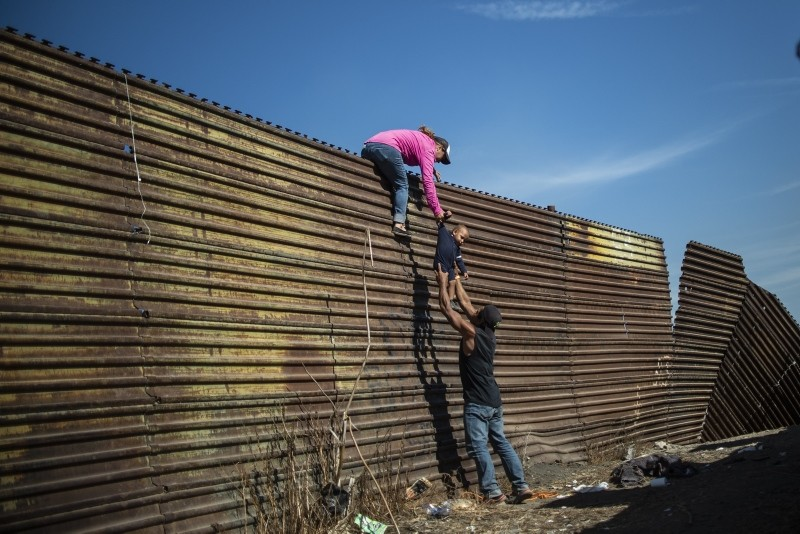 A group of Central American migrants climb the border fence between Mexico and the United States, near El Chaparral border crossing, in Tijuana, Baja California State, Mexico, on November 25, 2018. (AFP Photo)