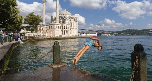 A young man jumps into the sea amid soaring temperatures, Istanbul, Aug. 3, 2019. AA Photo