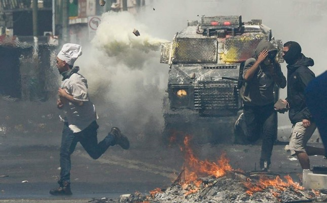 A man wearing a chef's hat runs for cover as anti-government protesters clash with police in Valparaiso, Chile, Thursday, Oct. 24, 2019. AP Photo