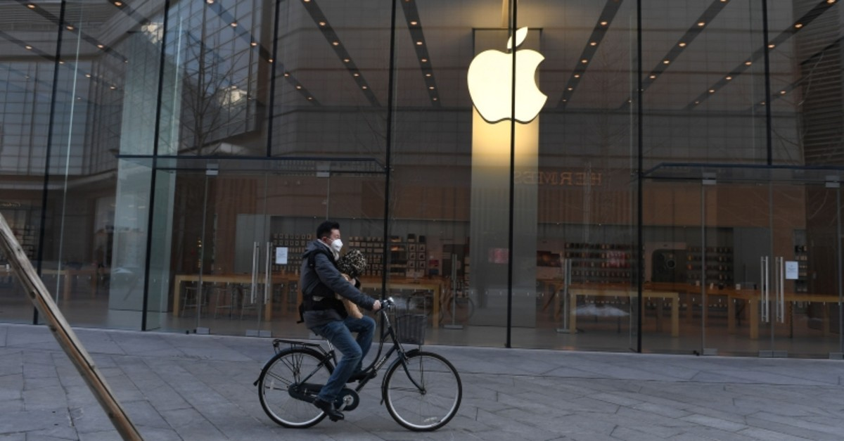 In this file photo taken on February 8, 2020 a man cycles past a closed Apple store in Beijing. (AFP Photo)