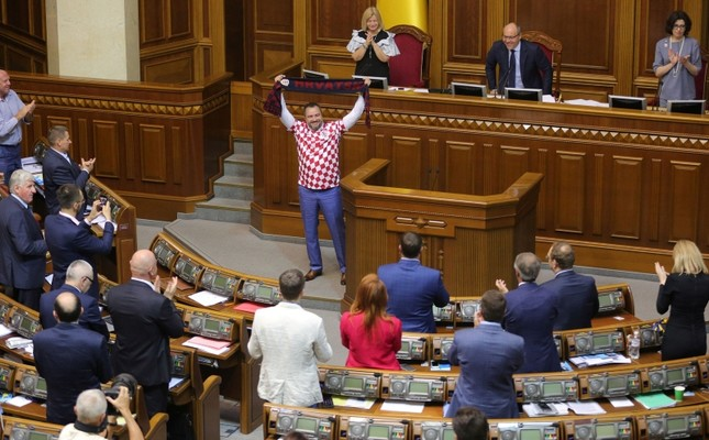 Ukraine football federation chief and lawmaker Andriy Pavelko, wearing a t-shirt of the Croatian football team, holds a scarf with the sign Croatia during the parliament session in Kiev, Ukraine, July 10, 2018. AFP Photo