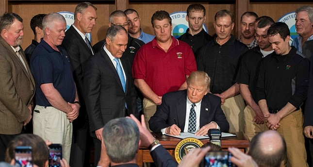 Surrounded by miners from Rosebud Mining, US President Donald Trump (C) signs he Energy Independence Executive Order at the Environmental Protection Agency (EPA) Headquarters in Washington, DC, March 28, 2017 (AFP Photo)