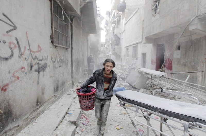 A boy carries his belongings at a site hit by what activists said was a barrel bomb dropped by forces loyal to Bashar al-Assad in Aleppo's al-Fardous district, Syria April 2, 2015. (Reuters Photo)