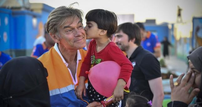 الجراح التركي الأمريكي أوز أثناء زيارته لمخيم اللاجئين في أعزاز (وكالة الأناضول للأنباء)