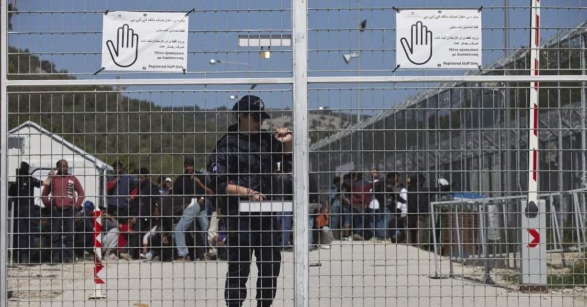 A Greek police officer closes the main gate of Moria camp as behind her refugees and migrants protest inside the entrance of Moria camp in the Greek island of Lesbos, Apr. 5, 2016. (AP Photo)
