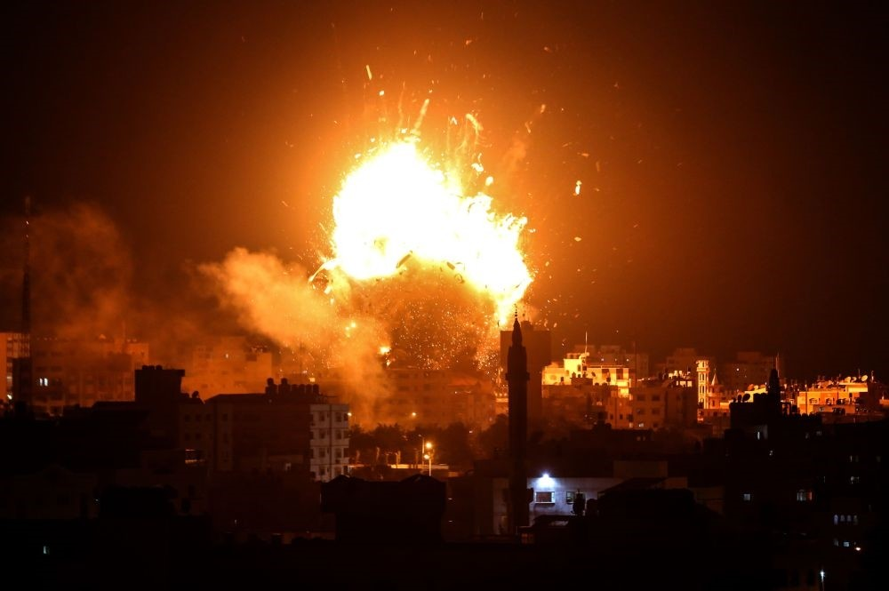 A ball of fire rises above buildings in the Gaza Strip during an Israeli airstrike; the incursion killed at least six civilians, Nov. 12.