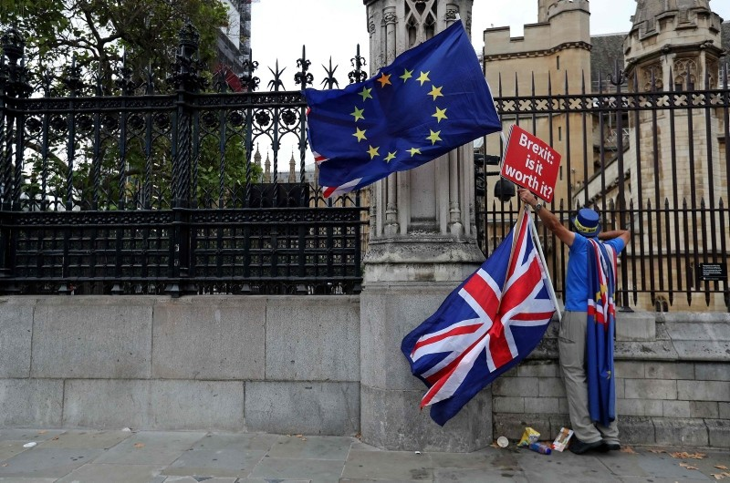 A demonstrator holds a sign that reads ,Brexit. Is it worth it?, whilst waving a European Union (EU) and Union flag, as he protests outside the Houses of Parliament in central London on September 11, 2018. (AFP Photo)