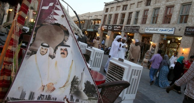 Taken in 2014, the photo shows people walking past a banner bearing portraits of former Emir of Qatar Sheikh Hamad bin Halifa al Thani R and his son current leader SheikhTamim bin Hamad al Thani displayed at Souq Waqf in Qatar capital Doha.