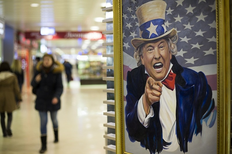 In this file photo taken on Wednesday, March 22, 2017, People walk past a caricature picture of U.S. President Donald Trump on sale in a shopping mall in Moscow, Russia. (AP Photo)