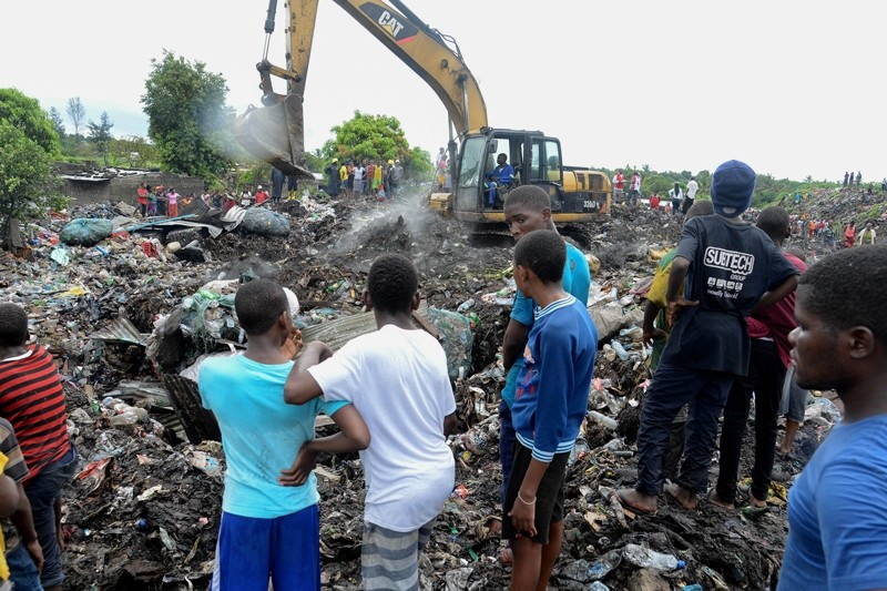 People watch rescuers using heavy machinery as they search for bodies of victims buried under collapsed garbage piles in Maputo, Mozambique, 19 February 2018. (EPA Photo)