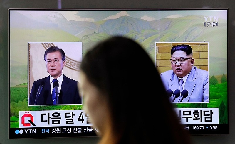 a visitor walks by a TV screen showing file footages of South Korean President Moon Jae-in, left, and North Korean leader Kim Jong Un, right, during a news program at the Seoul Railway Station in Seoul (AP Photo)