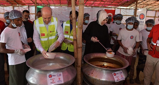Culture and Tourism Minister Numan Kurtulmuş, left, and his wife Sevgi Kurtulmuş distributing food a Rohingya refugee camp in Bangladesh, Feb. 7, 2018. (AA Photo)