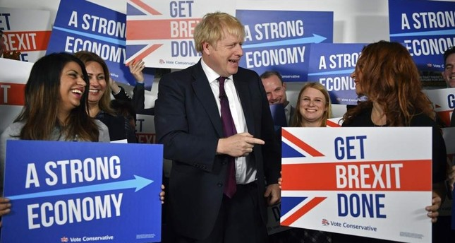 Britain's Prime Minister Boris Johnson center speaks to activists and supporters as he poses for a photograph at the Conservative Campaign Headquarters Call Centre, while on the General Election trail, London, Dec. 8, 2019. AP