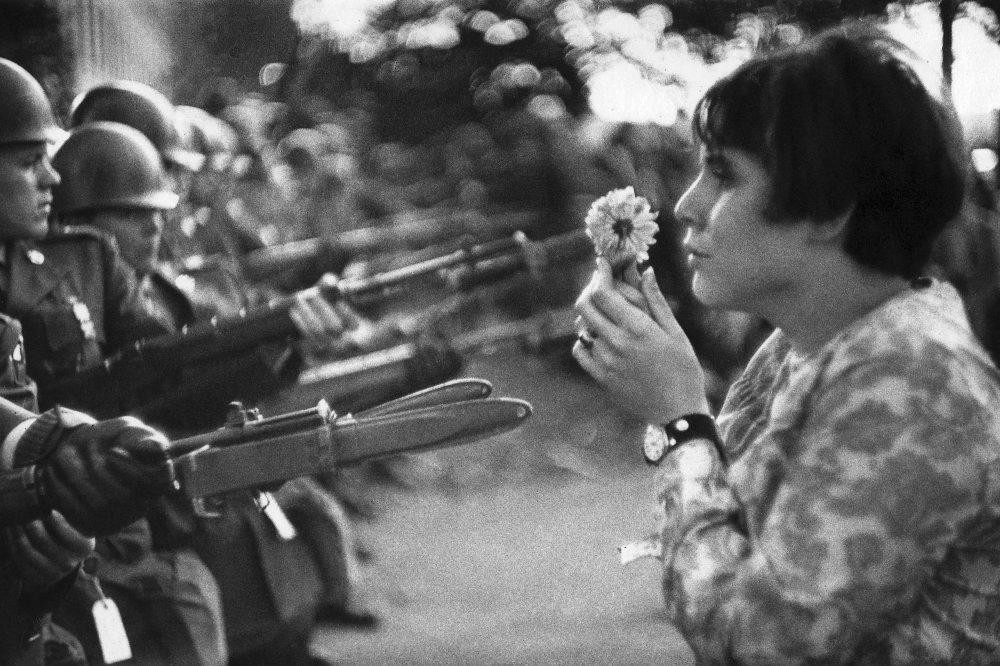 Jane Rose Kasmir holds a flower up to soldiers during an anti-Vietnam war demonstration outside the Pentagon, Oct. 21, 1967.