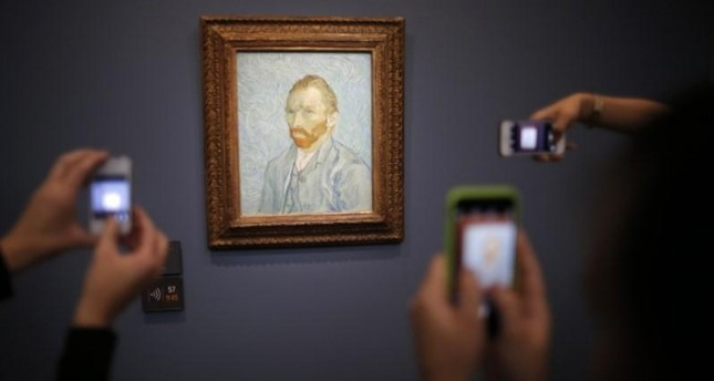 Visitors take pictures with their mobile phone of the painting Portrait de l'Artiste, 1889 (Self-Portrait) by artist Vincent van Gogh (1853-1890) at the Musee d'Orsay in Paris, France, July 28, 2015.
