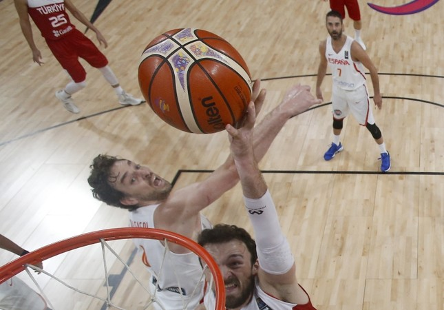 Sertaç Şanlı jumps to score a basket as Spain's Pau Gasol tries to stop him during their Eurobasket round of 16 match in Istanbul.