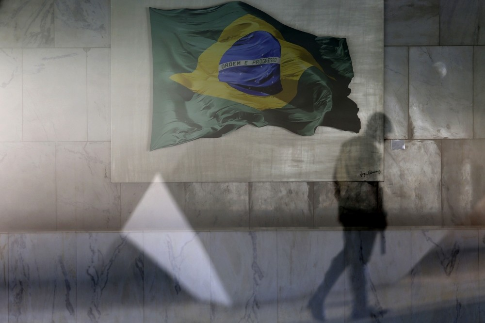 A presidential guard walks past a window allowing a view into the Planalto presidential palaceu2019s main lounge, decorated with an image of a Brazilian national flag, in Brasilia.