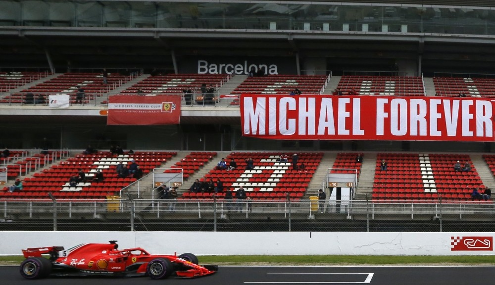 Ferrari driver Sebastian Vettel of Germany drives by a tribute-banner in honor of former German driver Michael Schumacher during a Formula One pre-season testing session in Barcelona.