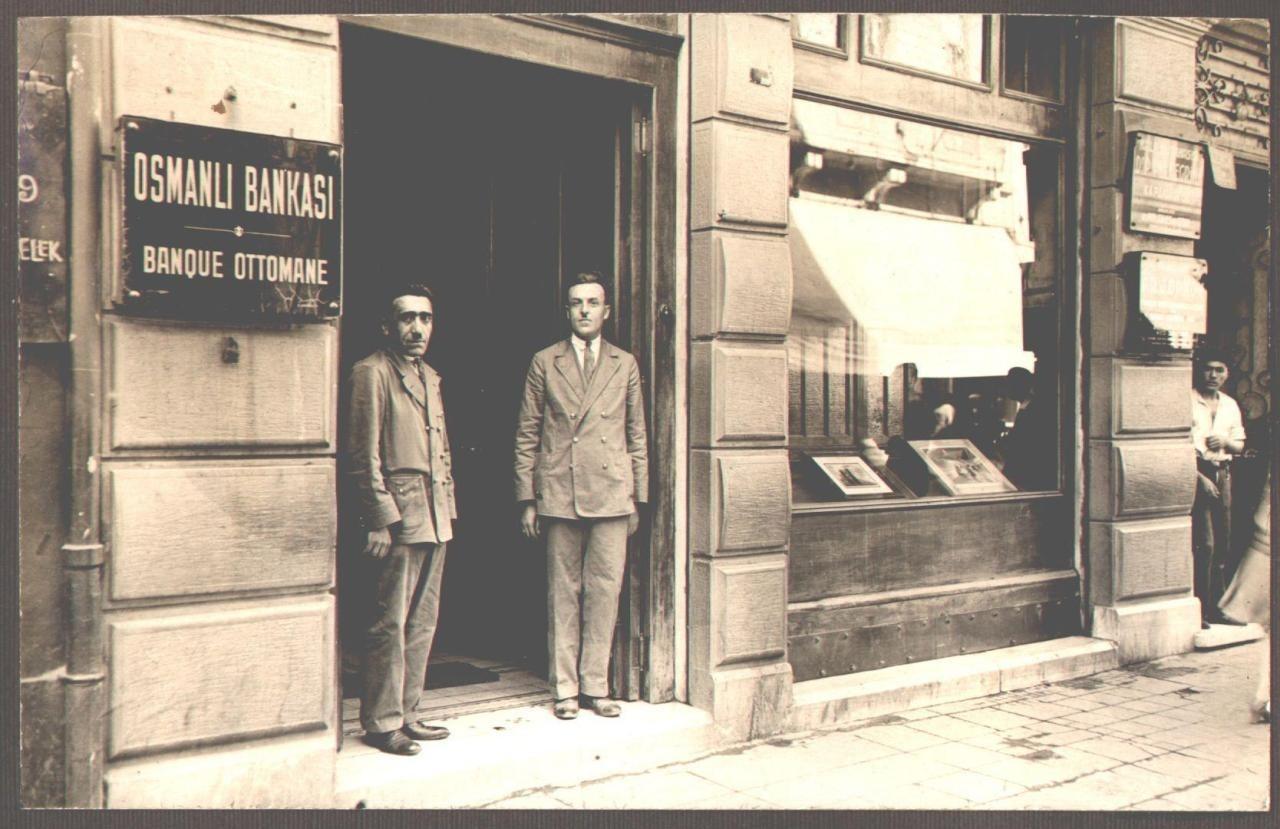 Two men stand at the entrance of the Ottoman Banku2019s Beyou011flu branch circa 1930.