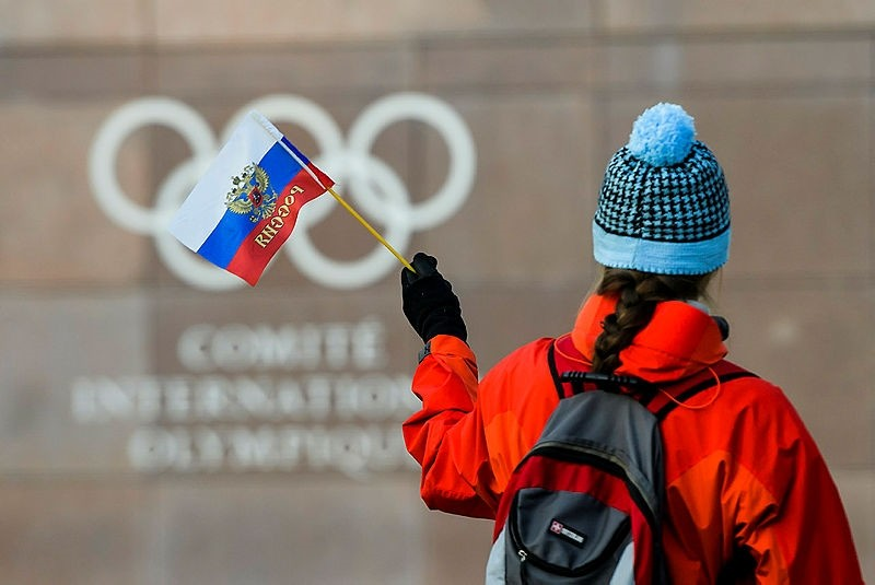 A woman holds a Russian flag in front of the Olympic Rings logo during the Executive Board meeting, at the International Olympic Committee (IOC) headquarters, in Pully near Lausanne, Switzerland, Dec. 5. (AP Photo)