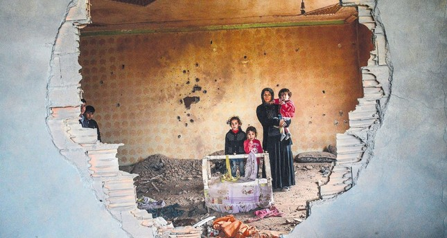 A woman and her children stand in the ruins of a house damaged by PKK terrorists clashing with security forces in the predominantly Kurdish town of Silopi, southeastern Turkey, January 19, 2016.