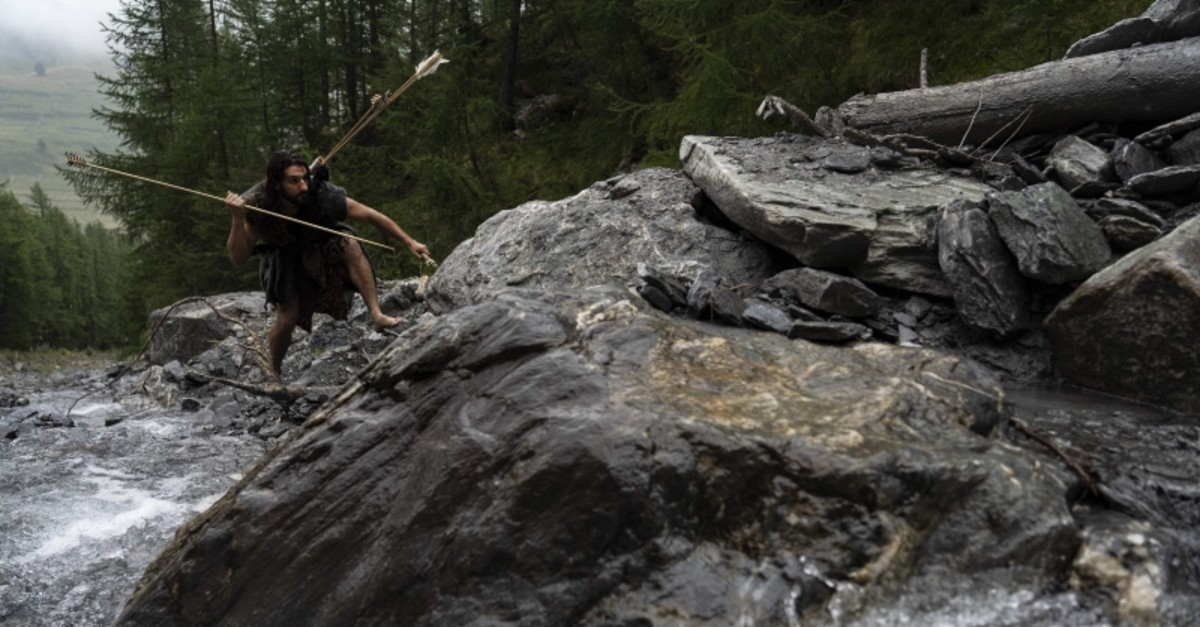 Guido Camia dressed as a Neanderthal Cave man tries to catch a fish in a river in Chianale, in the Italian Alps, near the French border, on Aug. 7, 2019 (AFP Photo)