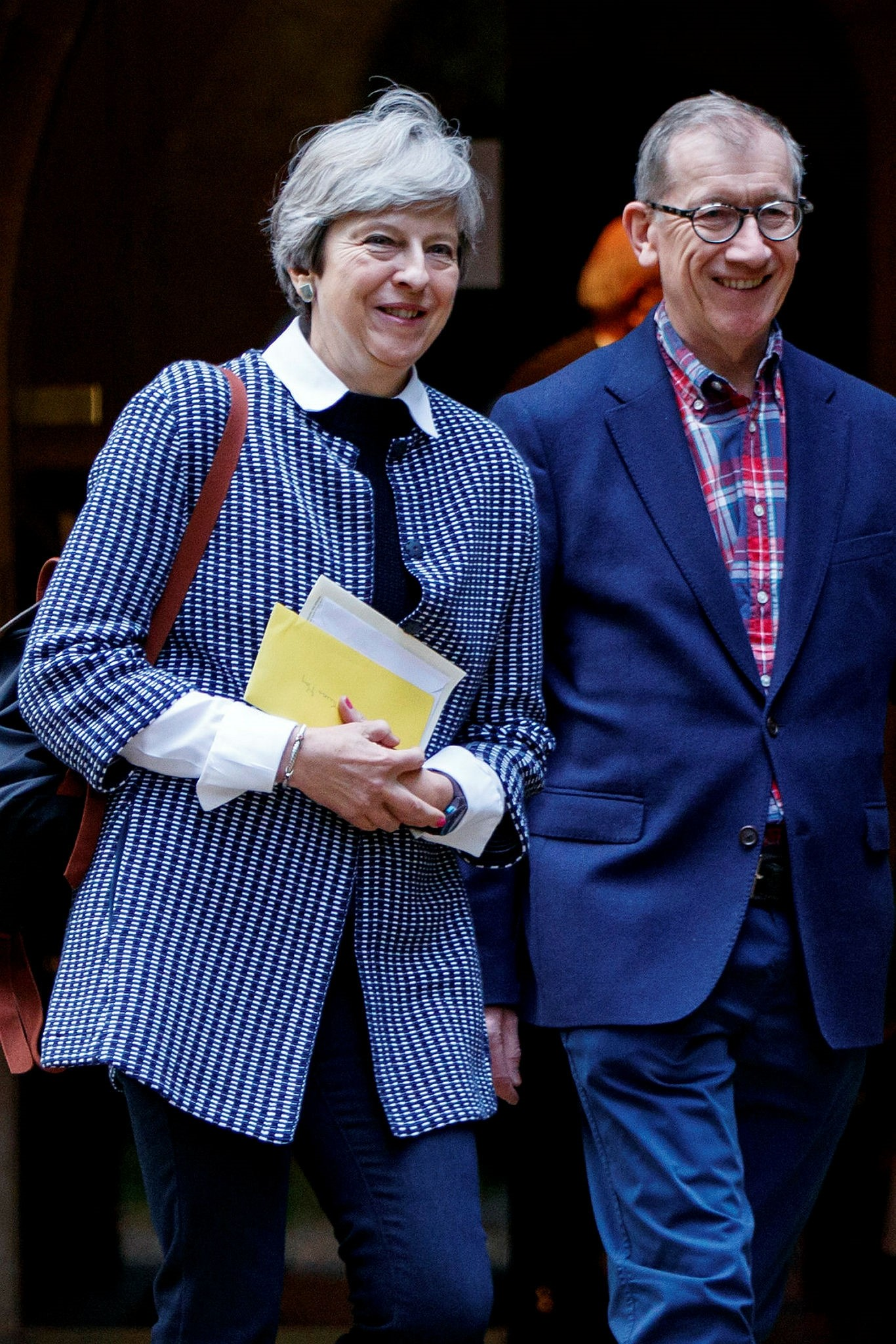 British Prime Minister Theresa May (L) and her husband Philip May leave after attending the Sunday morning service at a church in her Maidenhead constituency in Berkshire, Oct. 8.