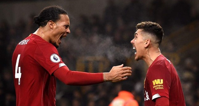 Liverpool's Virgil van Dijk L and Roberto Firmino celebrate the team's second goal against Wolves, Jan. 23, 2020.