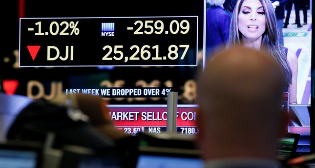 A trader looks at a screen that displays the Dow Jones Industrial Average on the floor of the New York Stock Exchange, (NYSE) in New York, U.S., February 5, 2018. (REUTERS Photo)
