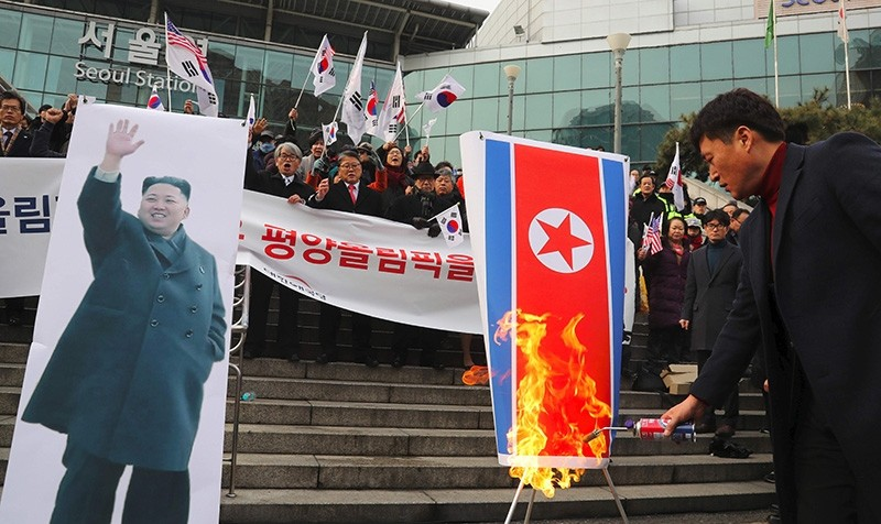 South Korean protesters burn a North Korean flag (R) and a picture (L) of North Korean leader Kim Jong-Un during an anti-North Korea rally outside Seoul station in Seoul on Jan. 22, 2018. (AFP Image)