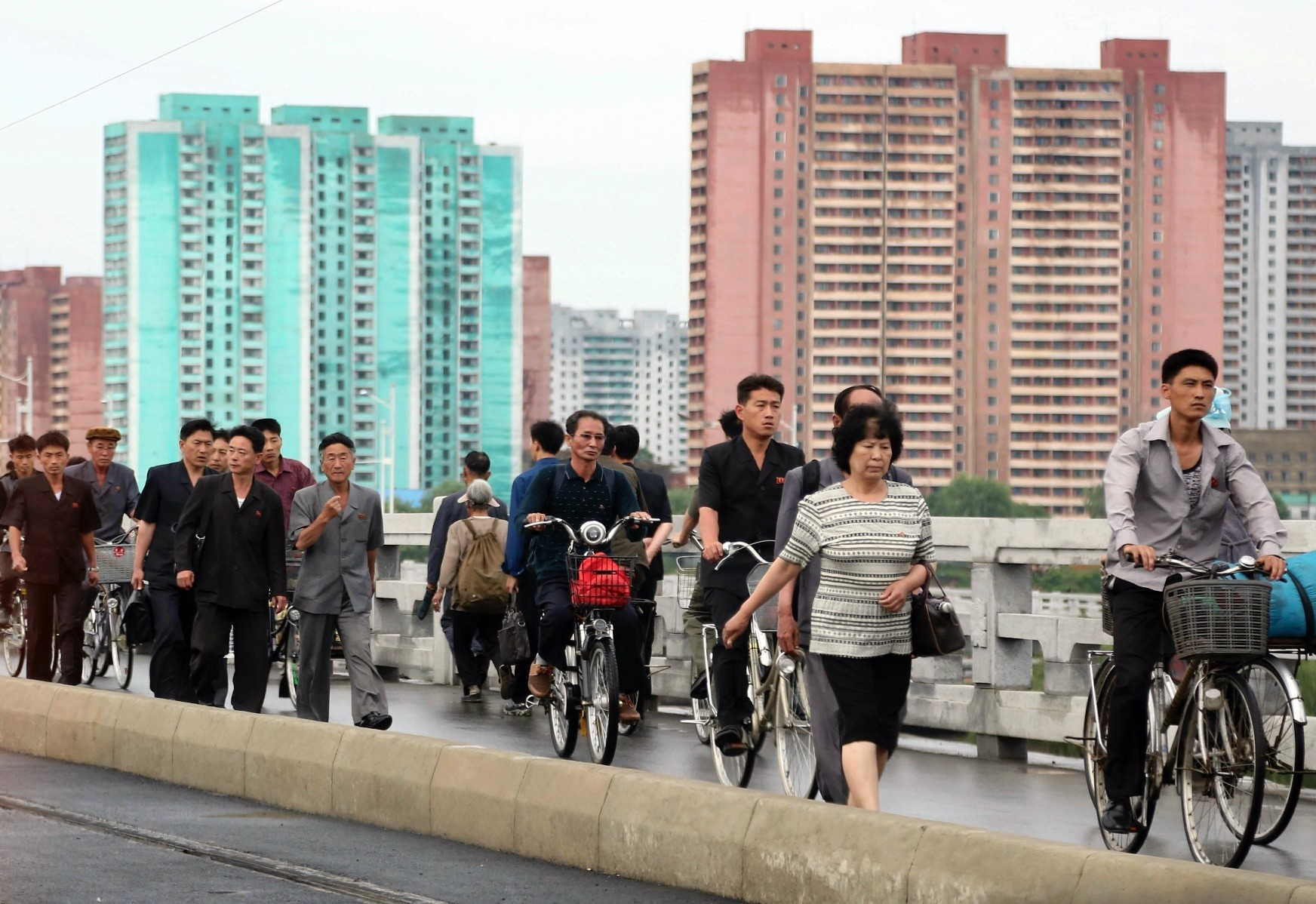 Men and women walk on a bridge as apartment buildings are seen in the background during the morning rush hour in Pyongyang. High rise apartments are a common form of accommodation for people living in the capital city.