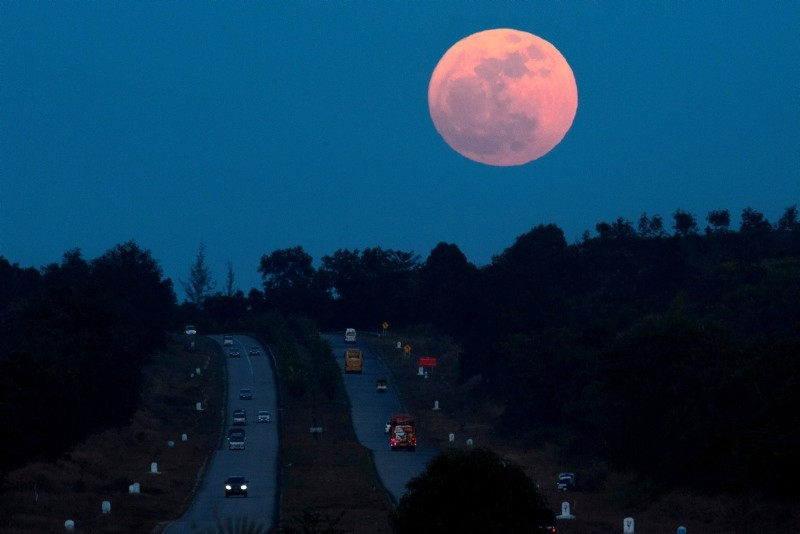 The supermoon rises over a highway near Yangon on December 3, 2017 (AFP Photo)