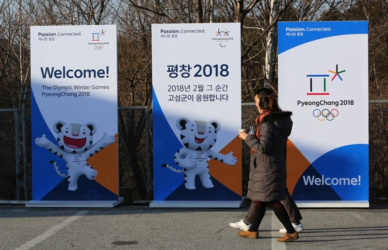 A couple passes posters showing the 2018 Pyeongchang Winter Olympic mascot at the Unification Observation post in Goseong, near the border with North Korea, South Korea (AP Photo)
