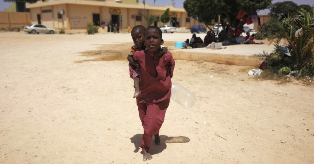 A migrant child carries another child on her back in the Ganfouda detention center west of Benghazi, Libya, July 10, 2019.
