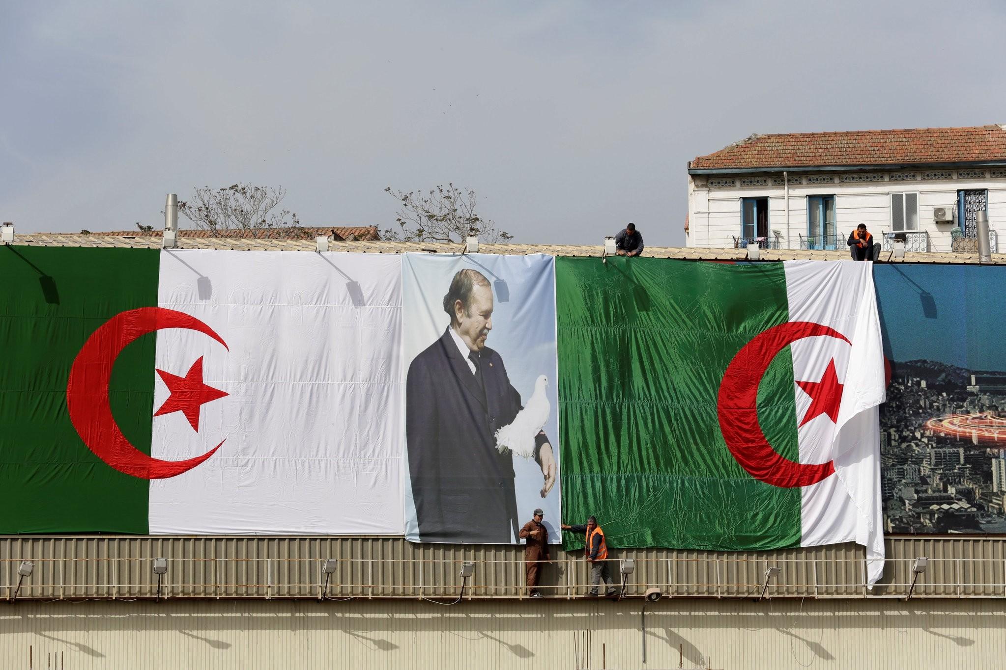Algerian city employees install Algerian flags and President's Abdelaziz Bouteflika poster on the streets. (REUTERS Photo)