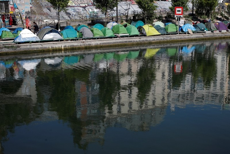 In this May 18, 2018 file photo, tents where asylum seekers live in a makeshift camp line up along the canal Saint-Martin in Paris. (AP Photo)