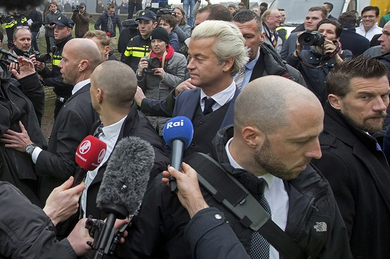 In this Saturday Feb. 18, 2017, image firebrand int-islam lawmaker Geert Wilders, center, is protected by police and security officers during an election campaign stop in Spijkenisse, near Rotterdam, Netherlands. (AP Photo)