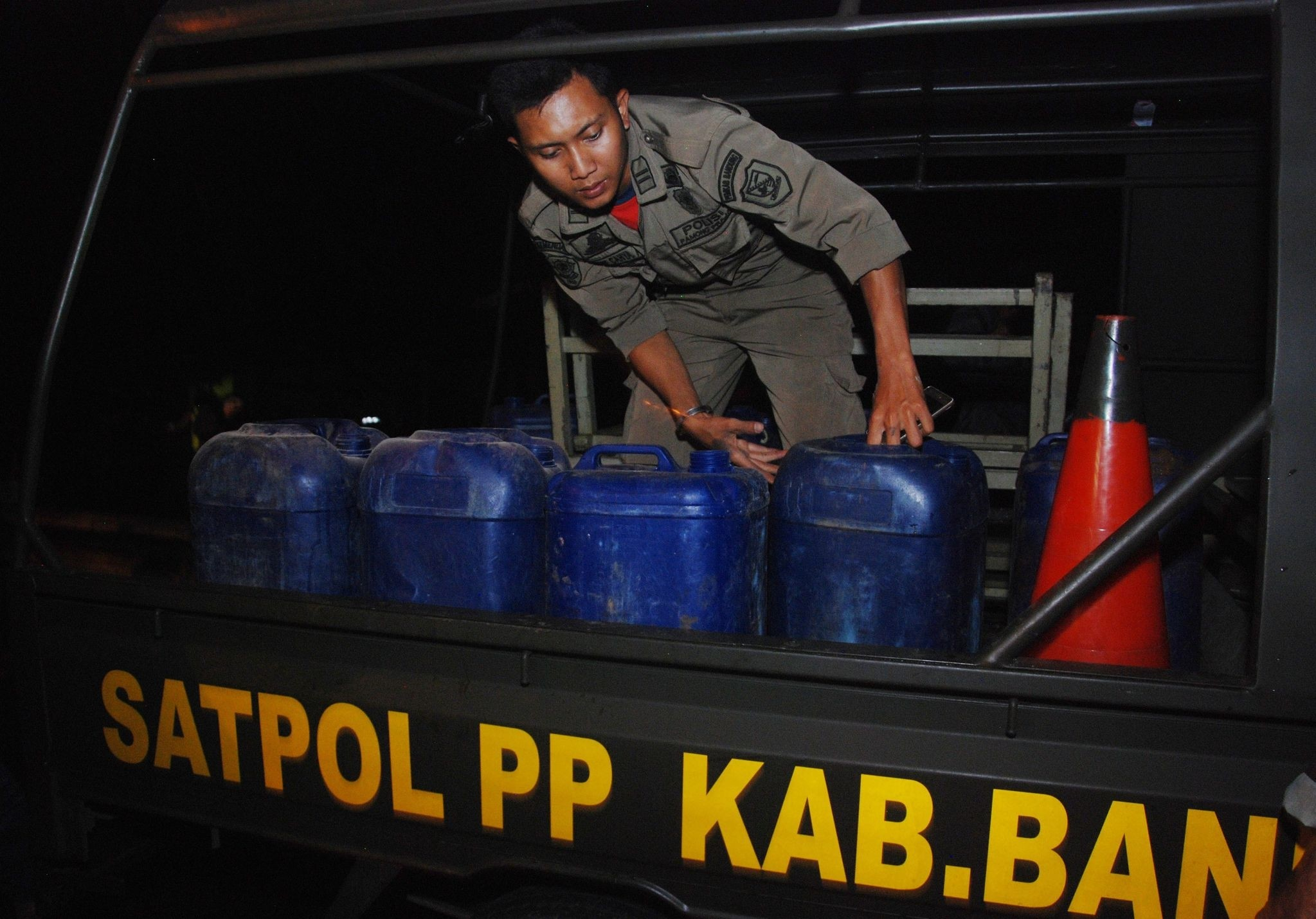 Indonesian police prepare to transport the containers filled with illegal alcohol from a house in Cicalengka district in West Java province on April 8, 2018. (AFP Photo)