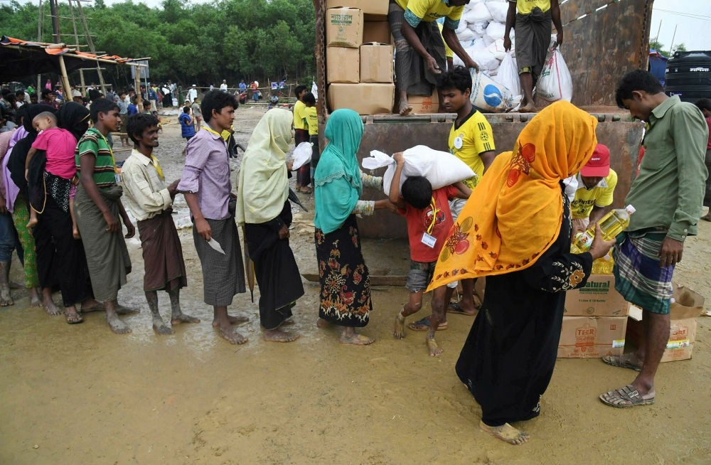Rohingya refugees wait to collect relief aid at the Thainkhali refugee camp in the Bangladeshi district of Ukhia, Nov. 1.