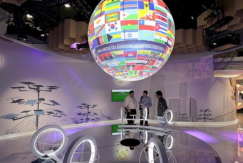 Visitors stand beneath a spinning Globe with the flags of the nations during the COP23 United Nations Climate Change Conference on November 7, 2017 in Bonn, western Germany. (AFP Photo)
