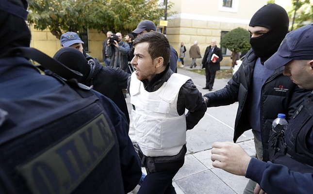 A Turkish suspect, no name available, is escorted by anti-terror police as he arrives at a court to face terrorism charges in Athens, Monday, Dec. 4, 2017. (AP Photo)
