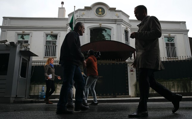 Pedestrians walk by as members of the media report from outside of Saudi Arabia's consul general's residence in Istanbul, Oct. 18.
