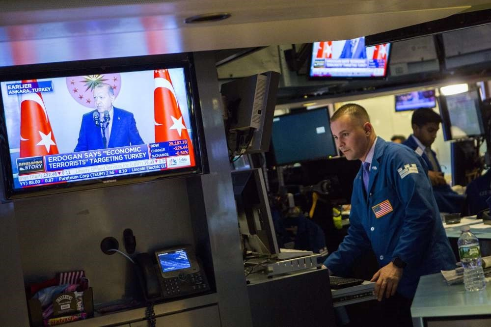 Traders on the floor of the New York Stock Exchange as President Erdou011fan (shown on TV) speaks about the U.S. attacks against the Turkish economy, Aug. 13.