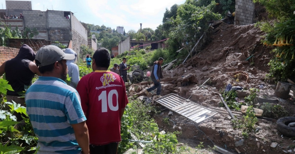 People walk at the scene of a deadly mudslide in Santo Tomas Chautla, Mexico, Thursday, July 11, 2019. (AP Photo)